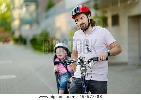 Young father and his cute little toddler daughter in a child seat getting ready to ride a bicycle