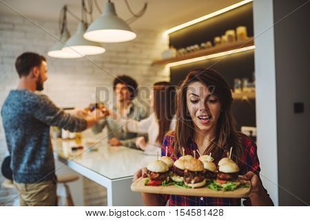 Beautiful young girl bringing more burgers to her friends.