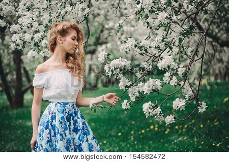 beautiful young woman in floral maxi skirt walking in spring