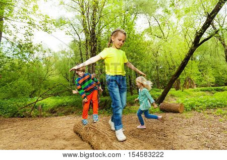 Portrait of happy kids balancing on a log walking one by one in summer forest