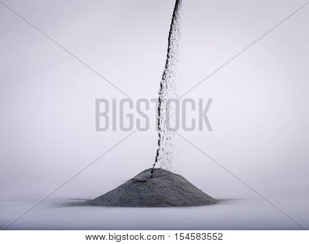 Pouring lead powder over gray background.