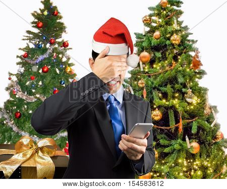 Portrait of an businessman covering his eyes because he not want to look the smart phone caller at christmas with santa hat
