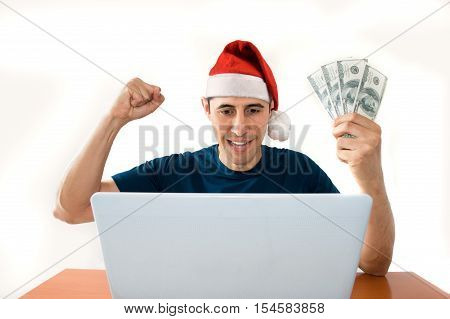 online betting man and making a lot of dollar at christmas with santa hat
