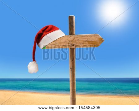 one wooden signpost in the beach with copyspace at Christmas with santa hat