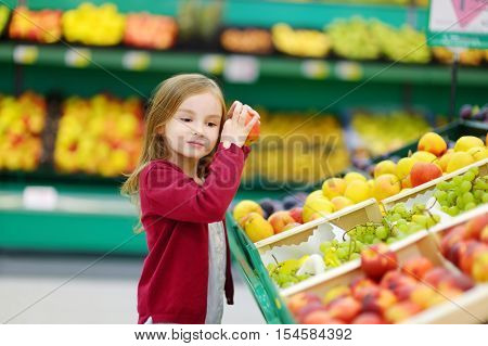 Little Girl Choosing An Apple In A Store