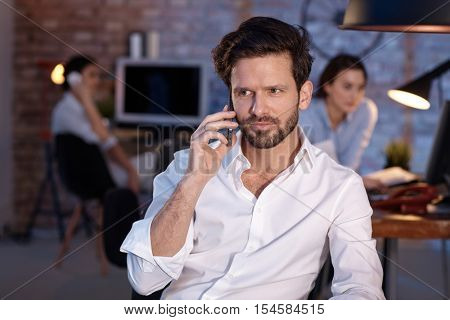 Businessman sitting in office, talking on mobilephone, looking away.