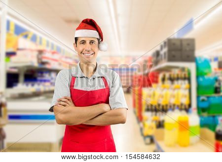 portrait of shopman at the supermarket with crossing arms wearing santa hat