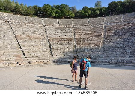 Epidavros Greece - Sept 23 2016: Tourists visit the ancient Theatre in Epidaurus built in 340 BC. This beautiful and best preserved theatre is on UNESCO World Heritage List since 1988