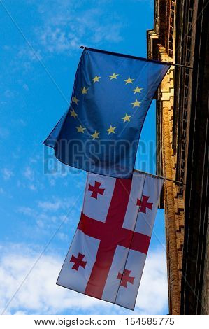 Flag of Georgia and the european union hang on a wall