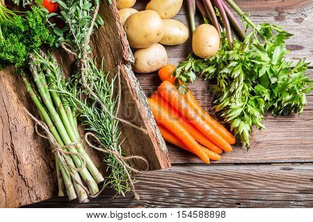 Fresh various vegetables on bark on old wooden table