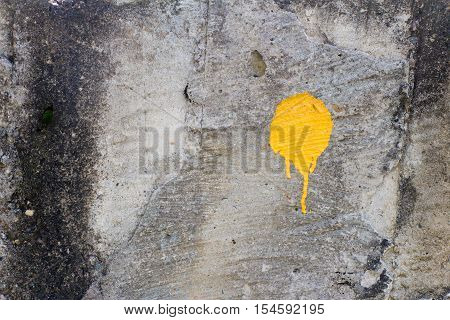 Yellow paint stain (one) on old and dirty wall. The surface of the concrete (stone) is not smooth.