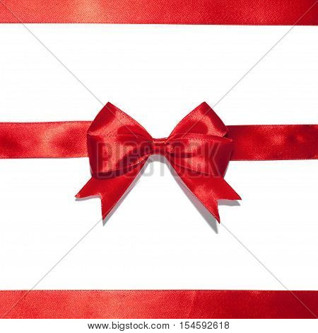 Red ribbon with bow on white. Studio shot