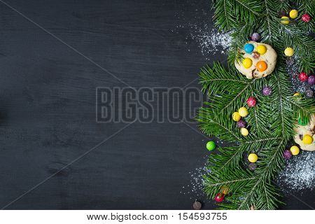 Christmas card. Space for text. Christmas tree on a black wooden background with sweets and biscuits. The original idea of Christmas. New Year. top view blank space for text Christmas. Copy Space.