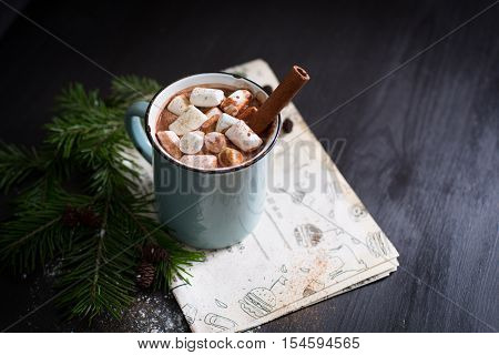 ot chocolate with marshmallows on the wooden black background  with kraft paper. Christmas tree with style.Hot cocoa with marshmallows.New Year.Christmas.Holiday card.Rustic style.Cinnamon.Copy Space
