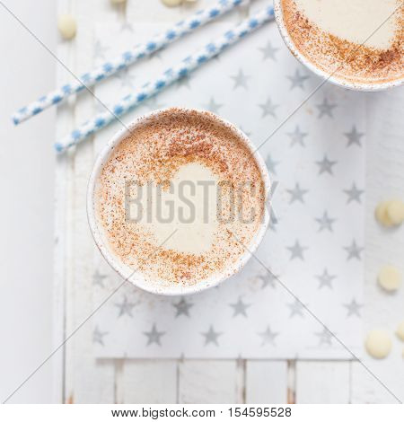 Milk tea with heart made of cinnamon on a white wooden background and kraft paper with stars. Space for text. Coffee.Cocoa.Cappuccino.Coffee. Hot drink.Christmas. Valentine's Day. New Year. Copy Space