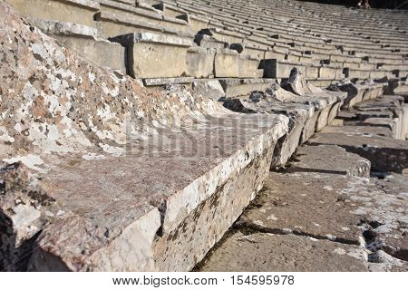 Greece. Site of the ancient Theatre in Epidaurus built in 340 BC. This beautiful and best preserved theatre is on UNESCO World Heritage List since 1988. Small depth of field
