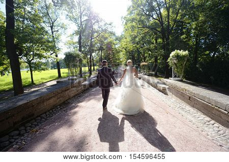 Wedding couple on the nature is walking. Beautiful model girl in white dress. Handsome man in suit. Beauty bride with groom. Female and male portrait. Woman with lace veil. Lady and guy outdoors