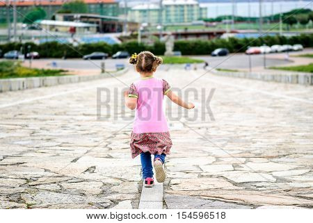 Little Girl Is Running On Stone Paved Promenade