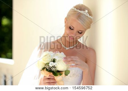 Beauty bride in bridal gown with bouquet and lace veil in the nature. Beautiful model girl in a white wedding dress. Female portrait in the park. Woman with hairstyle. Cute lady outdoors