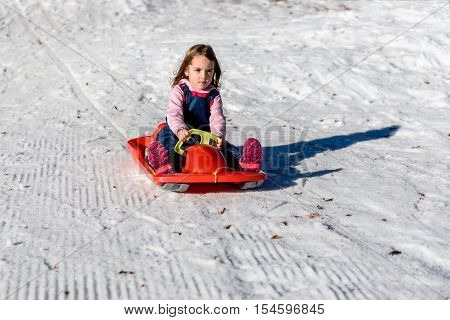 Little Girl Sliding With Bob In The Snow In Wintertime.