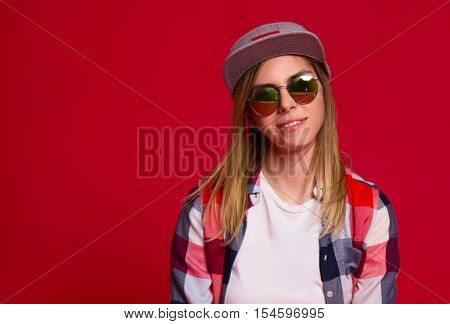 Fashion girl in a baseball cap and checkered shirt. Red background. Copy space.