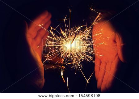 bright festive Christmas sparkler. Beautiful bright celebratory sparkler surrounded by female and male hands. Sparkler. Couple holding bengal light