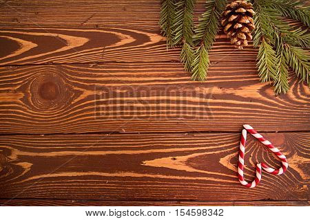Two red-white candy cane in shape of heart on wooden table. Top view. Image for greeting card with copy space