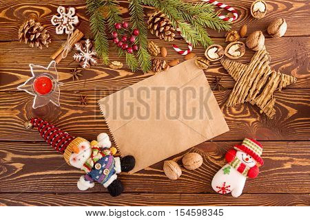Christmas decorations. Set for greeting card: branch of fir tree cones walnuts almonds gingerbread cookies candle snowmans. Top view. View from above. Copy space