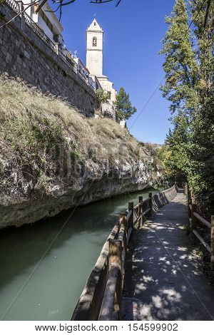 Alcala del Jucar Spain - October 29 2016: Passage along the river Jucar left the church of San Andres styles late Gothic and Neoclassic take in Alcala of the Jucar Albacete province Spain