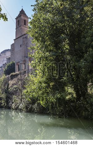 Alcala del Jucar Spain - October 29 2016: Passage along the river Jucar right the church of San Andres styles late Gothic and Neoclassic take in Alcala of the Jucar Albacete province Spain