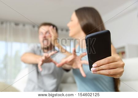 Angry couple or marriage fighting for a mobile phone at home