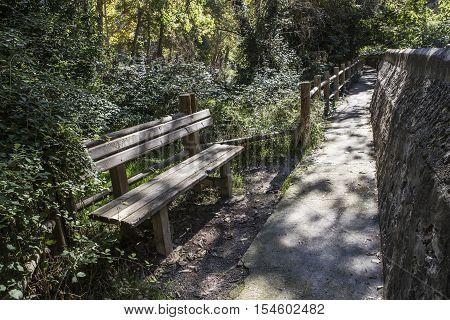 Alcala del Jucar Spain - October 29 2016: Passage along the river Jucar during autumn wooden bench take in Alcala of the Jucar Albacete province Spain