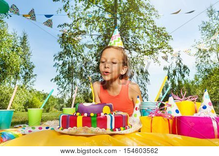 Adorable young girl in party hat blowing candles on birthday cake at the outdoor birthday party