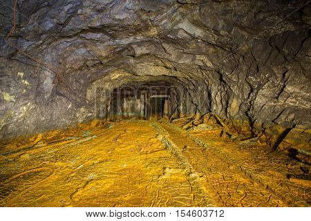 Old abandoned iron shaft mine tunnel with sulfur dirt