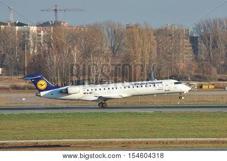 Borispol Ukraine - November 13 2010: Lufthansa Canadair CL-600 Regional Jet CRJ-701ER is landing on the runway with some buildings on the background