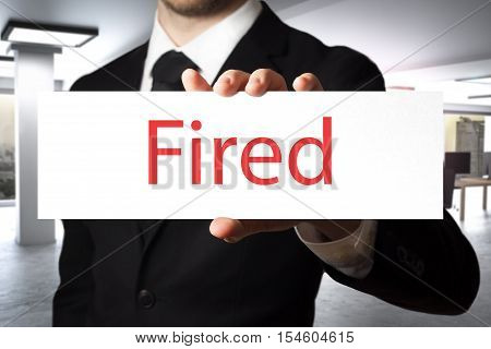 businessman in black suit holding sign fired