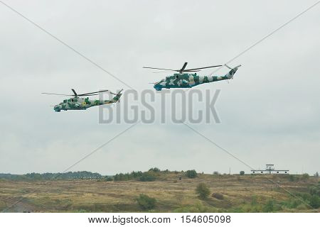 Zhitomir Ukraine - September 29 2010: A pair of Ukrainian Army Mi-24 attack helicopters in flight during military trainings - side view