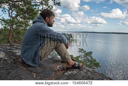 Man is sitting on the rock and looking into the distance