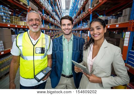 Portrait of warehouse team standing with digital tablet and barcode scanner in warehouse