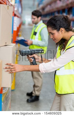 Female warehouse worker scanning box in warehouse