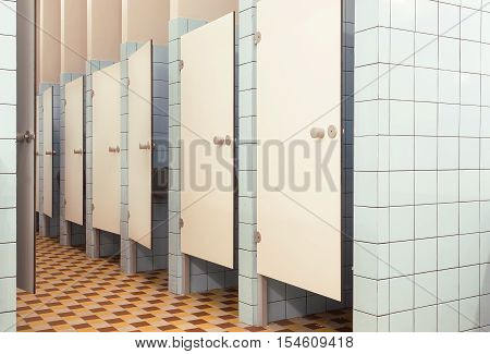 White doors in minimalistic interior of the public bathroom with toilet booths