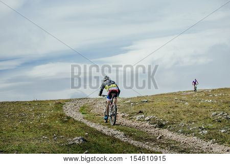two riders on sport bikes riding on a mountain trail on a blue sky background