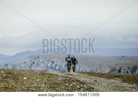 two cyclist on sports bikes riding on a mountain road. on background of mountains and sky