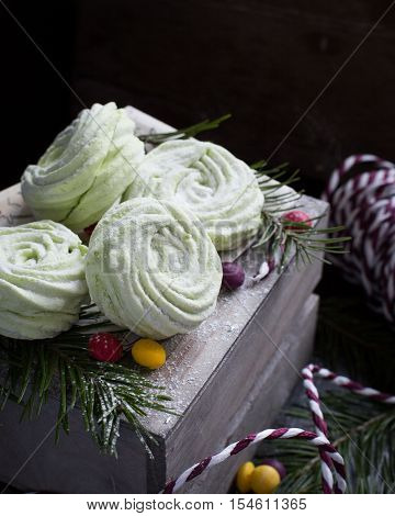 Apple marshmallows on the wooden box in the Christmas decoration. Beautiful Christmas card. The original idea. Spruce. New Year.
