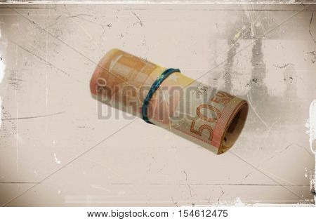 A roll with fifty euro banknotes on sepia background