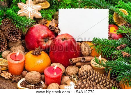 Christmas decoration burning candles and greetings card. Apples tangerine nuts spices and cookies