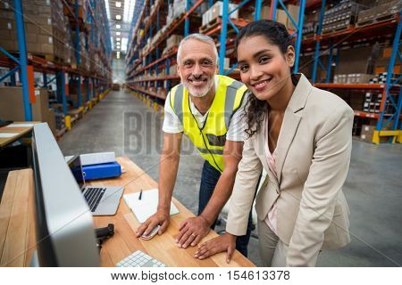 Portrait of warehouse manager and worker working together in warehouse office
