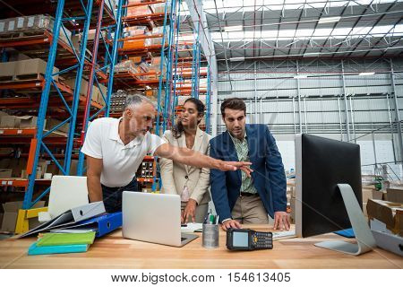 Warehouse managers and worker discussing with computer in warehouse office