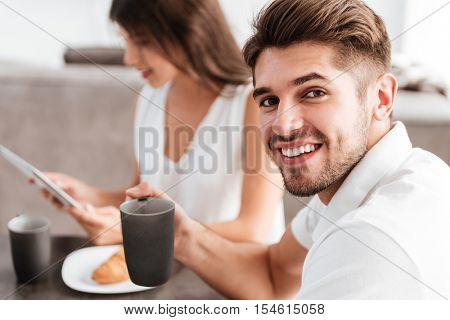 Cheerful young man drinking coffee while his girlfriend using tablet on the kitchen