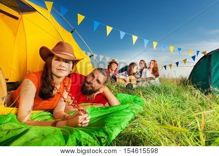 Portrait of happy young couple in tent enjoying camp trip in summer
